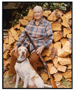 Dessie Prescott, holding a shotgun and sitting on a wood pile with dog at her feet.