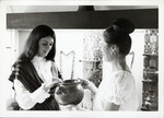 [Artifacts on display in the Pan American Center Museum with docents Janet Poole and Jean Babich, holding ceramic vessel]