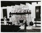 [Casa del Hidalgo interior, showing fireplace and associated artifacts with hostess Maria Hugas Acebal]